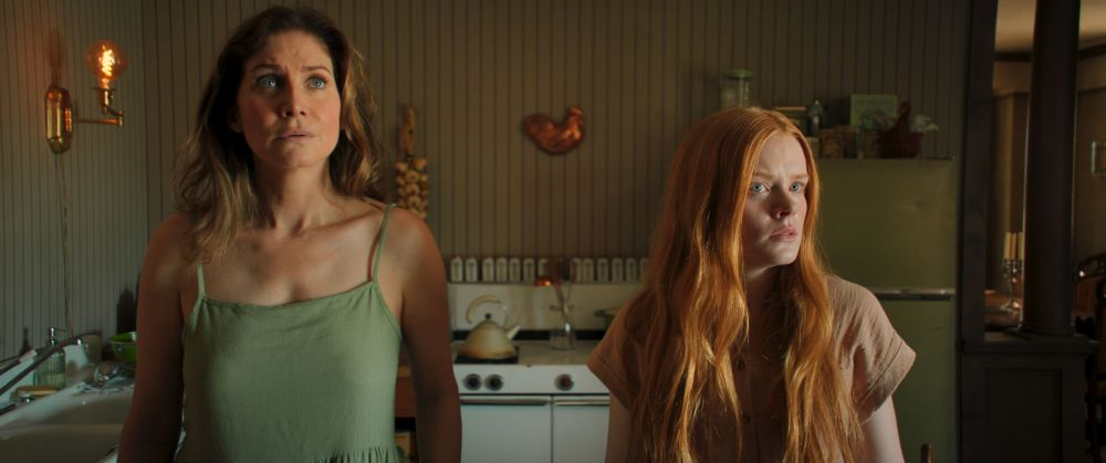 [L-R] Elizabeth Mitchell as Martha Goode and Abigail Cowen as Fiona in the thriller/horror film, WITCH HUNT, a Momentum Pictures release. Photo courtesy of Momentum Pictures